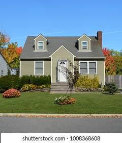Suburban Cape Cod style home Autumn season Blue Sky USA