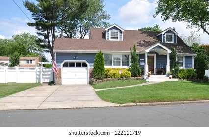 Suburban Cape Cod Style Home Cement Driveway Landscaped American Flag Sunny Day