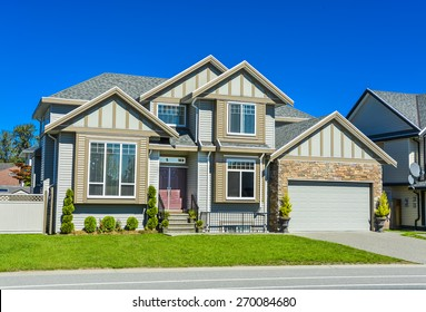 Suburban family house with concrete driveway, wide garage door on blue sky background.