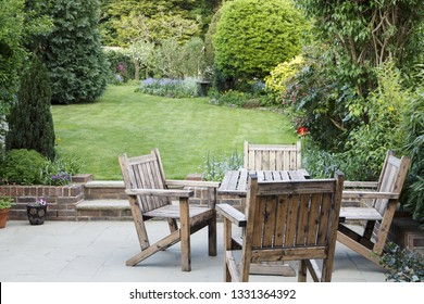 Suburban garden in London with wooden garden furniture on a patio