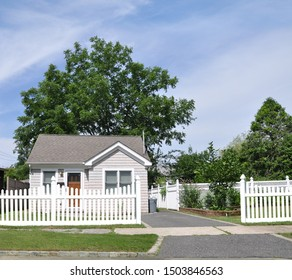 Suburban Gray single family Bungalow home with white picket fence blacktop driveway USA blue sky clouds