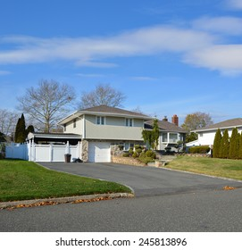 Suburban High Ranch Home with Siding and Stone Landscaped beautiful sunny blue sky clouds residential neighborhood USA
