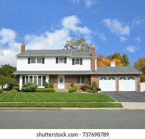Suburban High Ranch Home Two Car Garage Autumn Trees Blue sky clouds USA