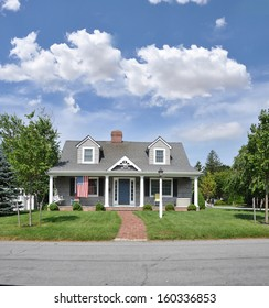 Suburban Home Cape Style Architecture American Flag Landscaped front yard brick walkway blue sky clouds USA