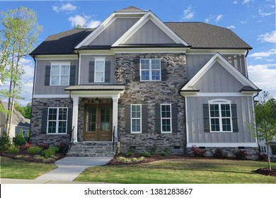 Suburban home with grey siding and stone exterior