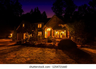 Suburban home at night with windows lit up and light spilling out onto the front lawn