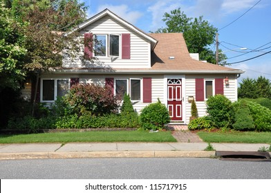 Suburban Home on middle class residential neighborhood street with gutter sunny blue sky day