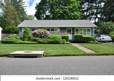 Suburban Home Ranch Style Landscaped Blooming Rhododendron and water drain at curbside of street