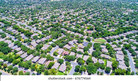 Suburban homes in Austin Texas USA aerial drone view during summertime green grass lush trees and endless houses and rooftops in the suburbs