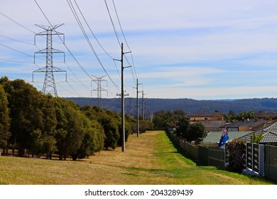 Suburban homes next to green grassed reserve with large overland powerlines and smaller local powerlines running parallel, with blue sky and white wispy cloud.