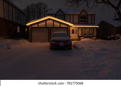 A Suburban House Covered with Snow and Lit Up With Clear Christmas Lights