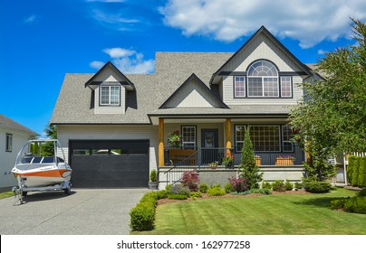 Suburban house with landscaping in front and blue sky background. Light powerboat parked on concrete driveway in front of the house.