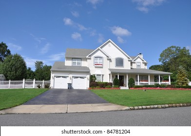 Suburban Luxury Home Blacktop Driveway with Trash Can Manicured Landscaped Front Yard