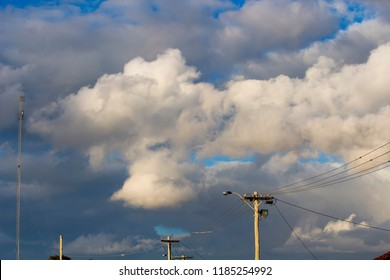 Suburban power lines and pole with fluffy pinky  white cumulus  cloud formations   with some cumulonimbus on  a sunny late afternoon  in late autumn  are contrasted against the blue Australian sky.
