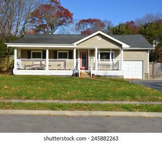 Suburban Ranch style home with porch sunny autumn day residential neighborhood clear blue sky USA