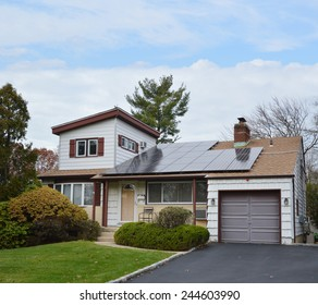 Suburban Ranch style home with solar panel on roof residential neighborhood USA blue sky clouds