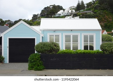 Suburban Seatoun housing, Wellington harbour with pale blue seaside cottage and background hills New Zealand