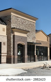 A suburban shopping center under construction.  A stone and brick storefront.