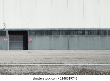 Suburban street background. An asphalt road in front of a white and gray building with a black rolling shutter on ground level. Prohibition signs to stop at its sides