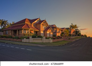 Suburban street corner with houses at sunset at Bella Vista, Sydney Australia. Typical upper middle class neighborhood in Australia. A wide Australian street with residential houses on a sunny day.
