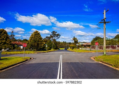 A suburban street crossroads with typical middle class houses in Blue Mountains Australia. A wide Australian street crossing with two stop signs and residential houses on a sunny day in the summer.