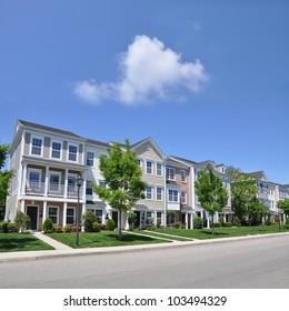 Suburban Three Story Condominiums along Street of Residential Neighborhood sunny blue sky day