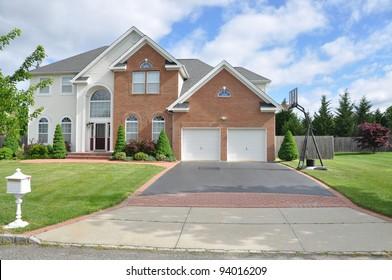 Suburban Two Car Garage  Blacktop Driveway with Basketball Hoop of Brick Home in residential suburban neighborhood