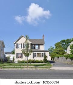 Suburban Two Story Home on Residential Neighborhood Street Sunny Blue Sky Day Cloud
