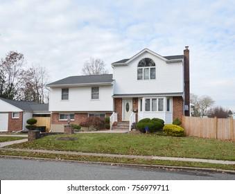 Suburban White And Brick Split Level Home Cloud Sky USA