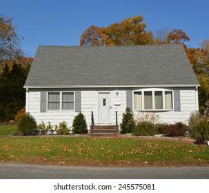 Suburban white and gray cape cod style home autumn day sunny clear blue sky residential neighborhood USA