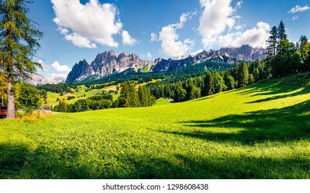 Suburbs of Cortina d'Ampezzo town are especially picturesque with their green meadows and majestic peaks of the mountains on background. Splendid summer scene of Dolomiti Alps, Italy, Europe.
