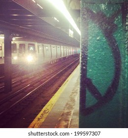 "Subway car traveling in motion underground with visible ""peace sign"" graffiti on pole in New York City with Instagram effect filter."