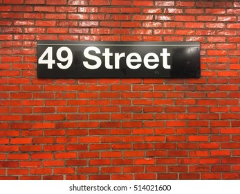 Subway station sign, 49 Street, on the red brick wall, New York