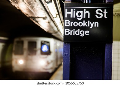 Subway train approaching behind the sign depicting it's the High St. Brooklyn Bridge station in Brooklyn, New-York.