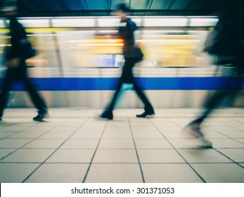 Subway train leaving station. People coming to or leaving the platform. Motion blur. City life. Slightly blue-toned.