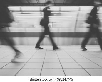 Subway train leaving station. People coming to or leaving the platform. Motion blur. City life.Black and white image.
