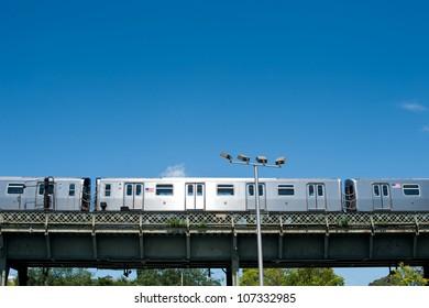 Subway train running outdoors in New York City.