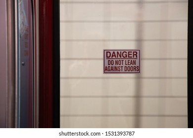 "Subway train sign reads, ""Danger Do Not Lean Against Doors"""