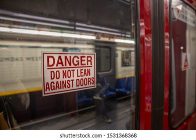"Subway train signage reads, ""Do Not Lean Against Doors"""