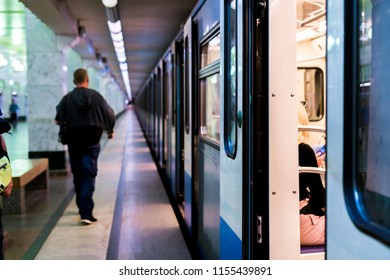 subway train staying on a metro station with doors open with defocused background
