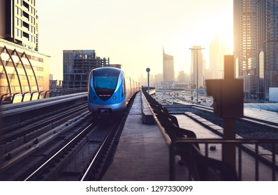 Subway train at sunset in modern city. Dubai metro. Downtown skyline with sundown. Skyscraper buildings and car traffic in the highway. Futuristic public transportation system.