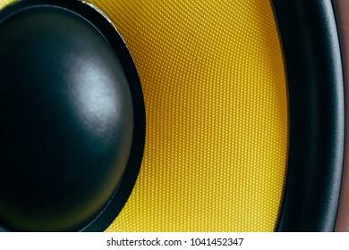 Subwoofer dynamic membrane or sound speaker as music background, yellow Hi-Fi loudspeaker close up macro shot