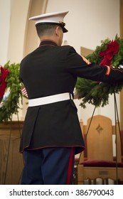SUCCASUNNA, NJ-DEC 12, 2015: A member of the U.S. Marine Corps places one of the ceremonial wreaths on its stand at the memorial service for the 2015 Wreaths Across America event.