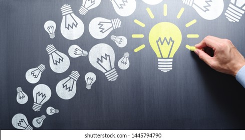 Succeed in finding solution after try and failure. Businessman drawing lightbulbs on chalkboard.