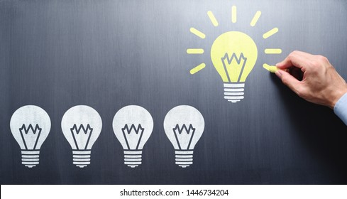 Succeed in finding solution. Businessman drawing lightbulbs on chalkboard.