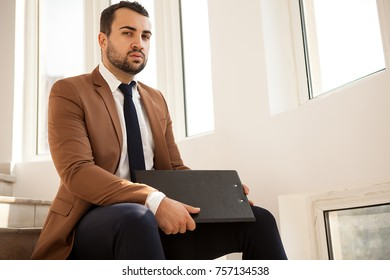 Succesful businessman sitting on stairs with a folder in hands on the hallway next to big windows