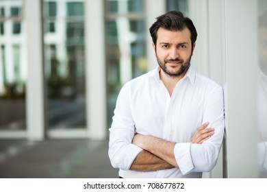 succesful man in white shirt standing next to an office building in a small break outside in a corporate area