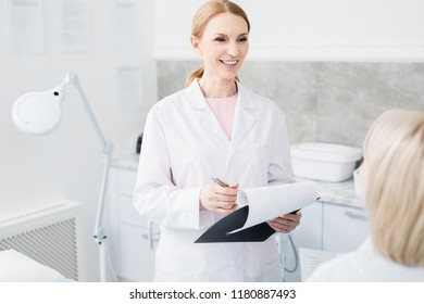 Succesful professional in whitecoat holding medical document while talking to her colleague at meeting