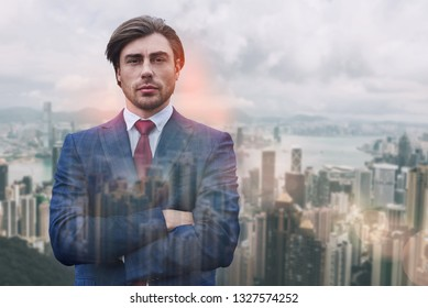 Succesful and rich. Close-up portrait of attractive man in suit keeping his arms crossed while standing against of cityscape background.