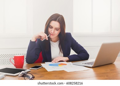 Succesfull woman, female carreer concept. Young businesswoman with laptop, concentrated at work. Modern office worker in white room interior.